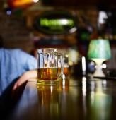 Vetro di birra chiara sul bancone bar in legno.