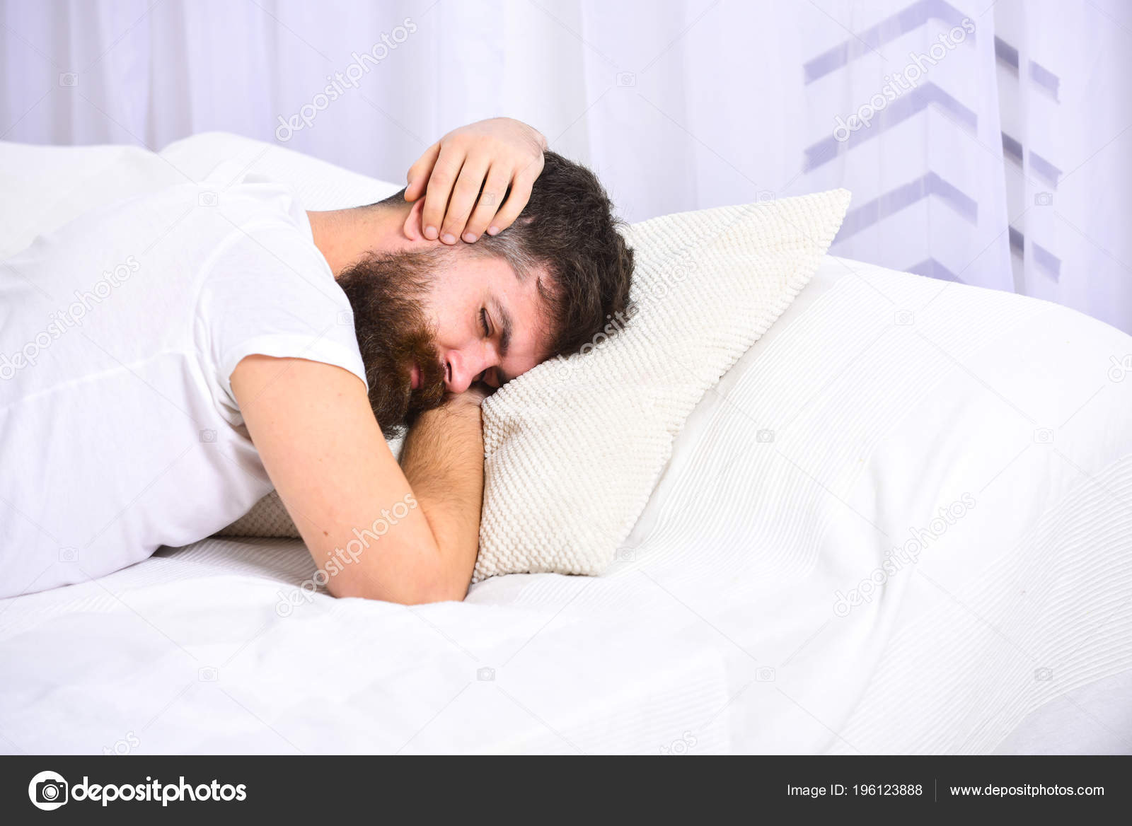 man in shirt laying on bed covering ears with hands white curtain