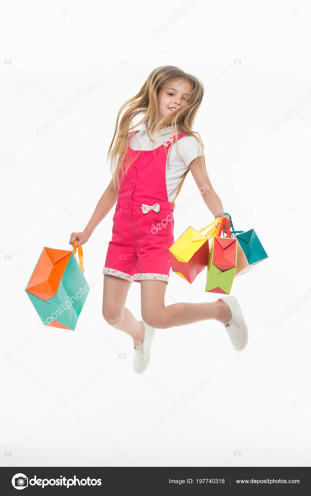 3f6b9404 Happy child jump with shopping bags isolated on white. Little girl smile  with paper bags.