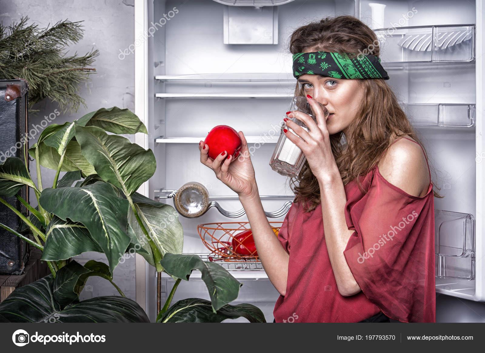 Senhora no rosto de um sonho à frente de frigorífico vazio aberto e bebidas  de leite. Conceito de dieta. Ela gosta de peso. Lady slim e skinny detém  apple. 3ad58910bc