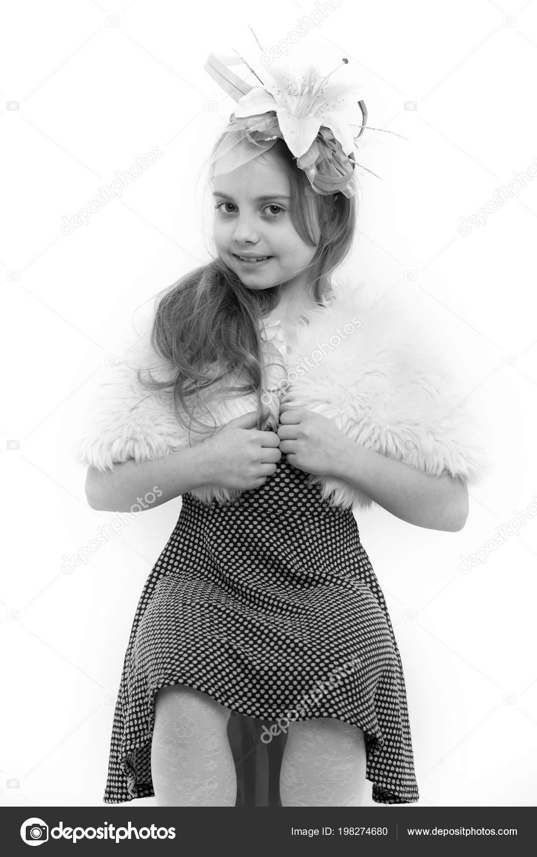 Sorriso della ragazza con il fiore in capelli biondi lunghi. Bambino  indossare abito e mantello di pelliccia. Moda e salone di bellezza. 88ff9680275