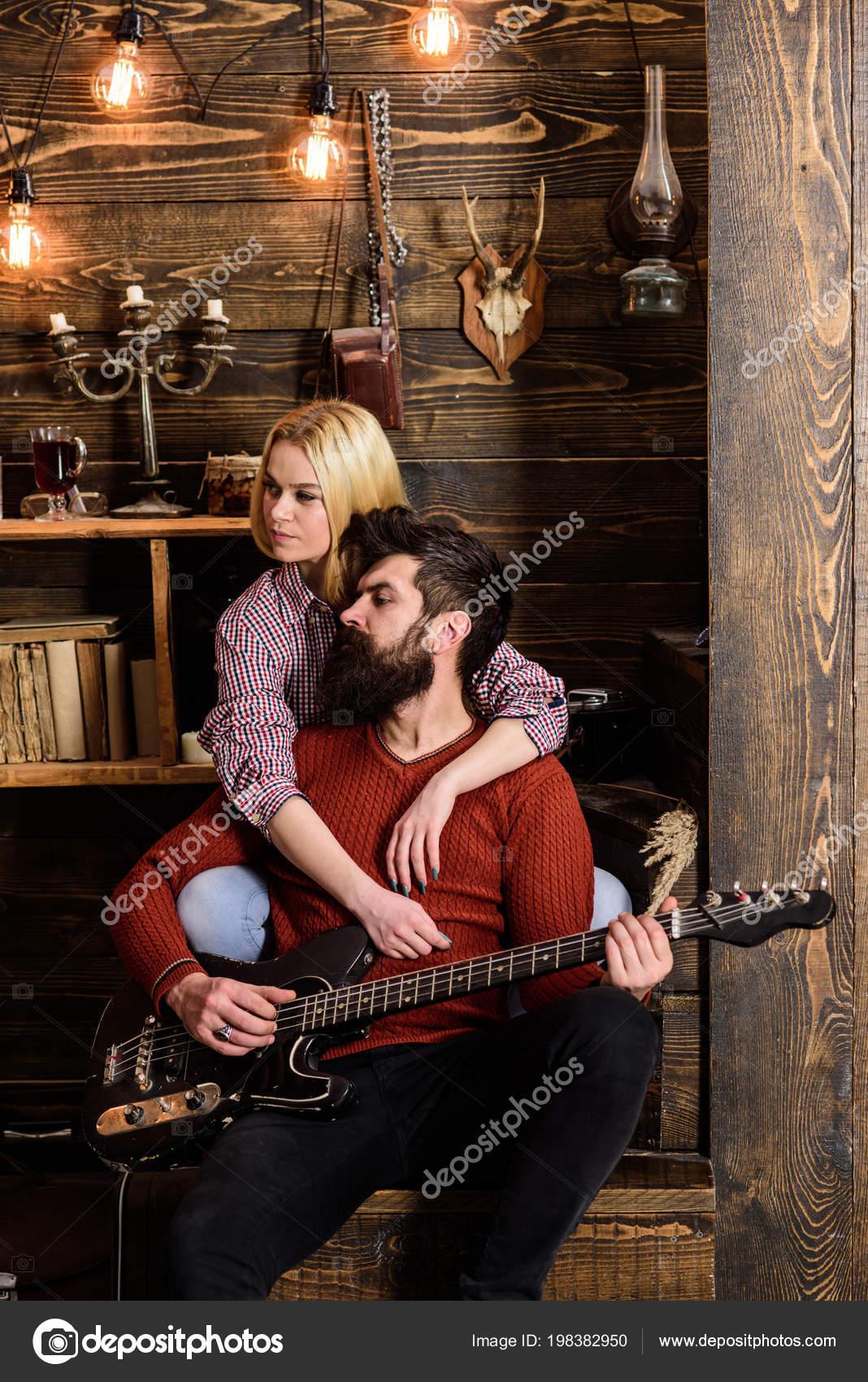 Paar im Interieur aus Holz Vintage Gitarrenmusik genießen. Frau und ...