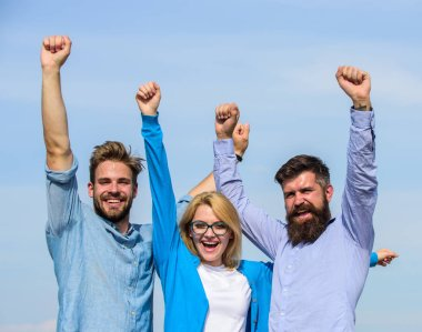 Company reached top. Men with beard in formal shirts and blonde in eyeglasses as successful team. Success concept. Company of three happy colleagues or partners celebrating success, sky background