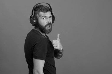 Music and leisure concept. Dj with beard wears headphones