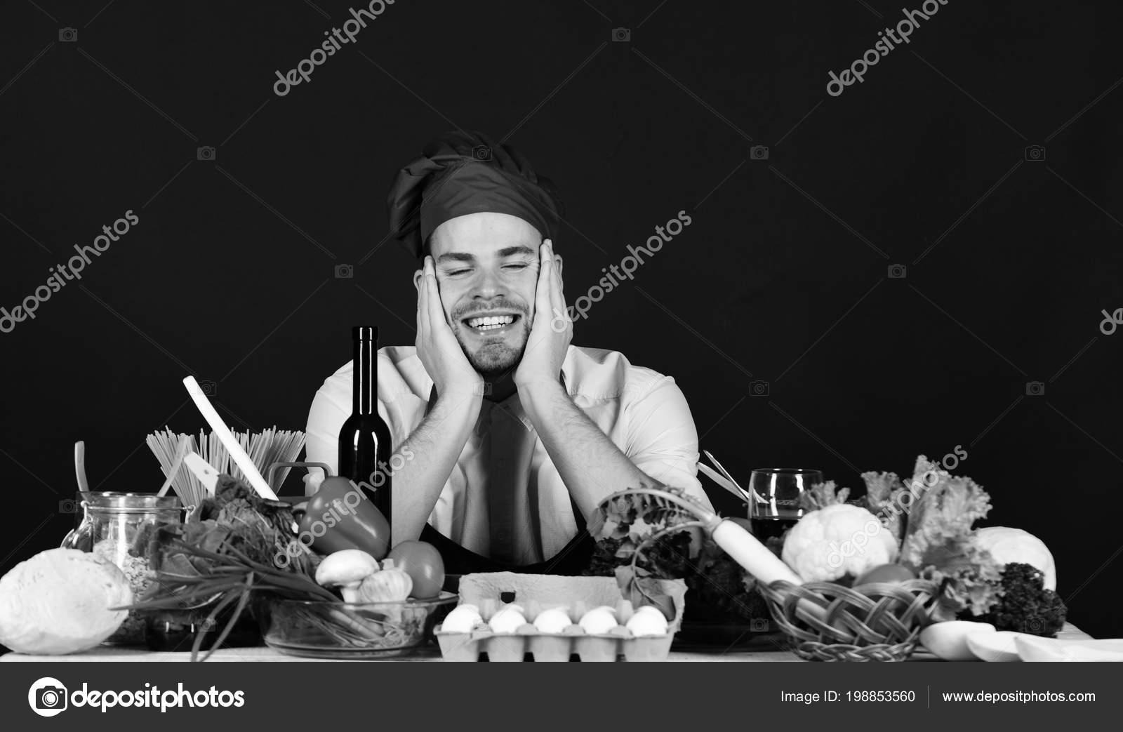 Cucina e concetto di cucina professionale. Uomo in Borgogna pose cappello e  grembiule vicino a cibo. Cuoco unico con la faccia da sogno su priorità  bassa ... 5ab36959608d