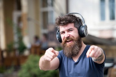 Hipster with headphones on happy face listening music and pointing forward. Music lover concept. Hipster with long beard and mustache with wireless headphones on head, defocused urban background