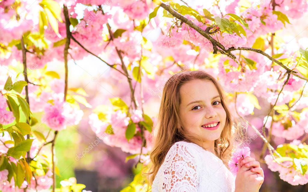 Cute child enjoy aroma of sakura on spring day. Girl on smiling face standing near sakura flowers, defocused. Girl with long hair outdoor, cherry blossom on background. Sweet childhood concept