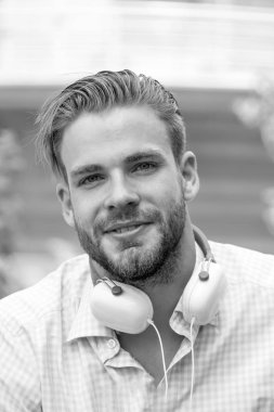 Man face. Handsome unshaven and young smiling man with headphones listening music outdoor on sunny day. Guy with headphones on neck.