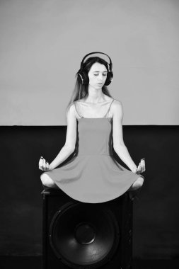 girl is listening to music. Dj sits on black loudspeaker on red and black background