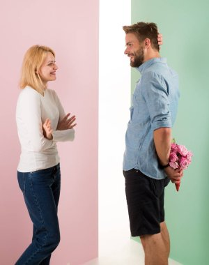 Clever attentive guy making surprise for holiday. Man with beard holds bouquet behind back. Surprise concept. Man congratulates woman birthday anniversary holiday. Couple in love celebrating holiday