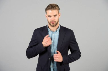 Formal menswear concept. Man bearded strict face wears formal clothes, grey background. Man with beard unshaven guy looks handsome and well groomed businessman. Guy bearded attractive with hairstyle