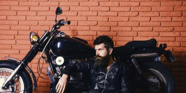 Brutal biker concept. Hipster, brutal biker on pensive face in leather jacket sit on floor near motorcycle. Man with beard, biker in leather jacket near motor bike in garage, brick wall background
