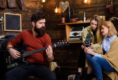 Man with trimmed beard playing electrical guitar. Rock musician spending time with family in countryside. Bearded man rehearsing at home. Girls shooting documentary about famous instrumentalis