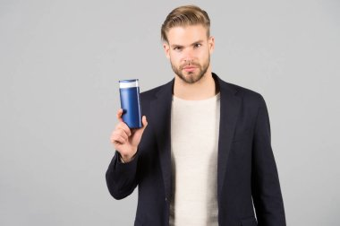 Man confident face holds shampoo bottle, grey background. Guy with bristle holds bottle shampoo, copy space. Man enjoy freshness after washing hair with shampoo. Hair care and beauty supplies concept