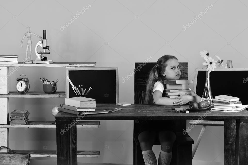 Girl sits at wooden desk with colorful stationery, flowers and fruit. Schoolgirl with grumpy face holds books stack