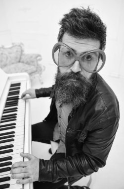 Comic performer concept. Man in leather jacket sits near piano musical instrument in white interior on background. Man, rock musician, pianist playing. Guy in giant red sunglasses while playing piano