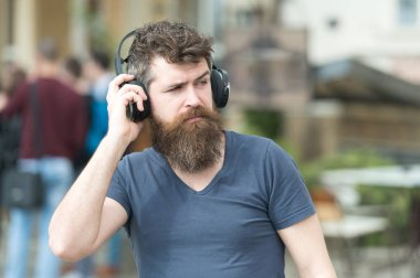 Music lover concept. Hipster with headphones on strict face listening music while walking. Man with long beard and mustache with wireless headphones on head, defocused urban background