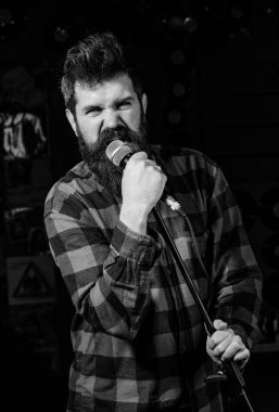 Man with tense face holds microphone, singing song, black background. Musician with beard and mustache singing song in karaoke. Vocalist concept. Guy likes to sing in aggressive manner