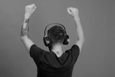 Man holds hands up and dances on blue background. Technologies and music concept. Dj with scorpio tattoo wears headphones