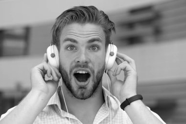 Music and sound concept. Man with unshaven face enjoy sound with modern headphones. Macho with surprised face likes music. Young man listening music