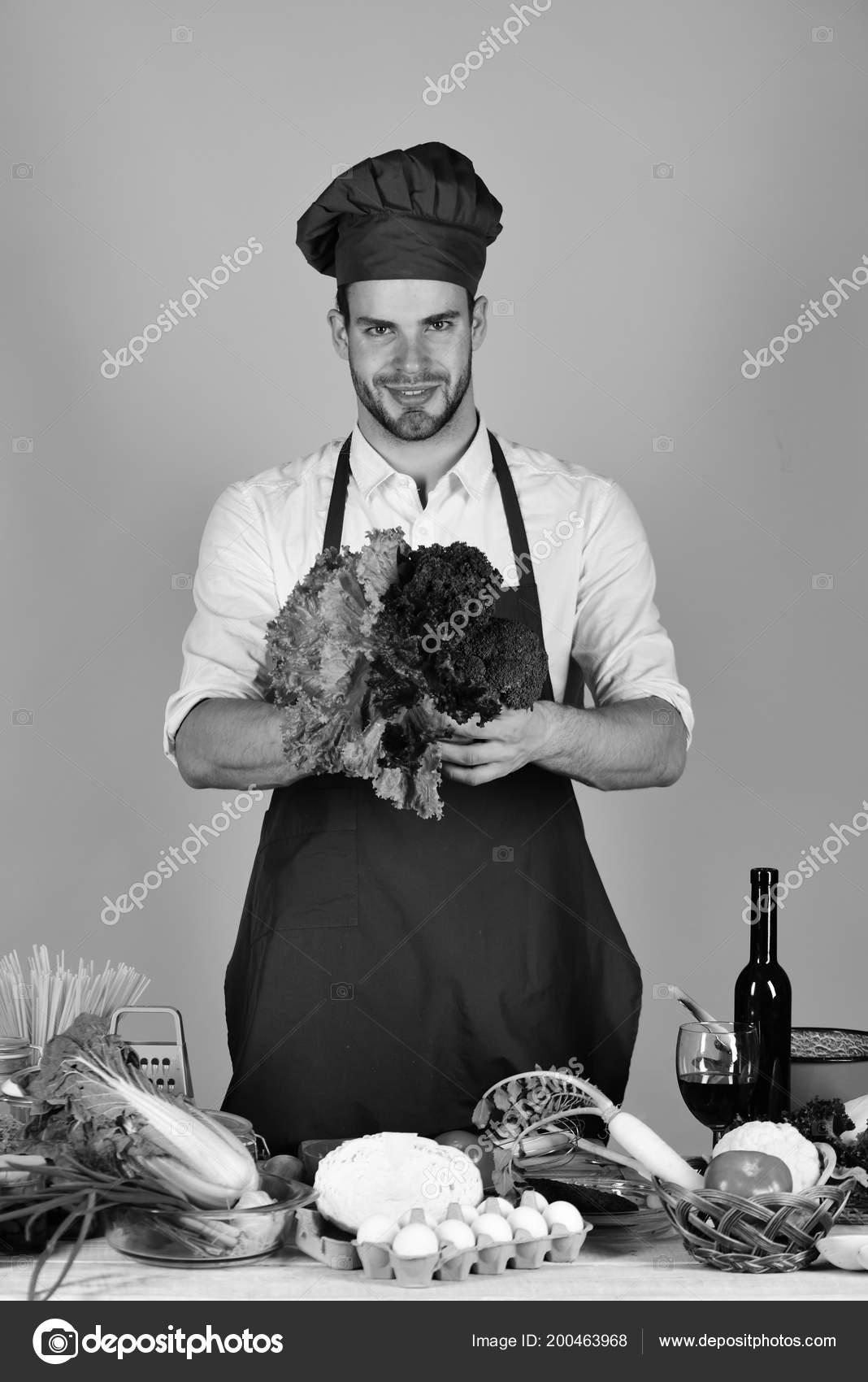 Uomo in cappello del cuoco e grembiule con insalata. Cook funziona in cucina  con le d920d1991f2d