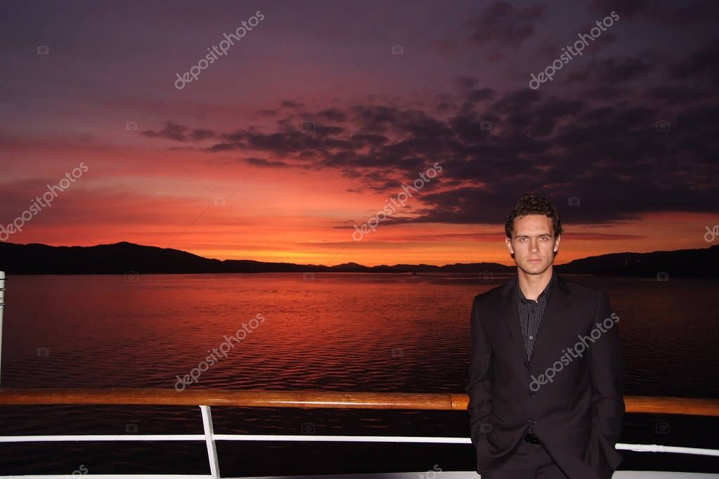 Man stand on ship deck on dramatic sky over sea in Bergen, Norway. Businessman enjoy sea travel in evening. Business or pleasure trip. Summer sea vacation. Adventure and wanderlust. Sunset or sunrise.