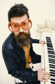 Fotografie Mann in riesige rote Sonnenbrille beim Klavierspielen. Comic-Künstler-Konzept. Mann in Lederjacke sitzt in der Nähe von Klavier Musikinstrument in weißen Innenraum auf Hintergrund. Mann, Rockmusiker, Pianist spielt