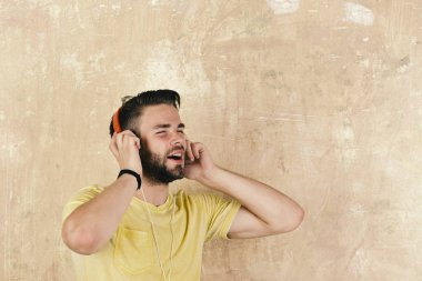 Musical lifestyle. Cheerful dj listening songs via earphones. European man have fun time. American handsome bearded guy with headphones.