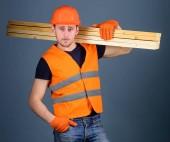 Fotografie Carpenter, woodworker, labourer, builder on confident face carries wooden beams on shoulder. Hardy labourer concept. Man in helmet, hard hat and protective gloves holds wooden beam, grey background