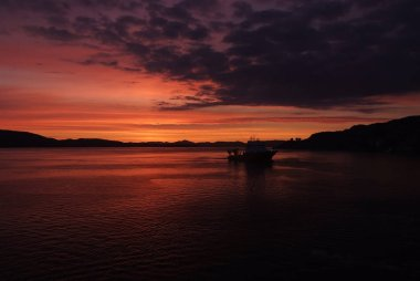 Seascape after sunset in Bergen, Norway. Ship in sea in evening dusk. Dramatic sky over sunset sea water. Traveling with adventures by ship. sunrise. Beauty of nature. Wanderlust and vacation.