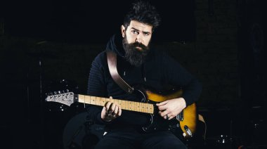 Play guitar concept. Musician with beard play electric guitar musical instrument.