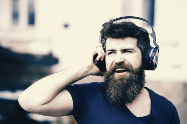 Fun, joy and music concept. Bearded hipster man wearing big earphones listening to music. Young man singing along to his favorite song while walking in city