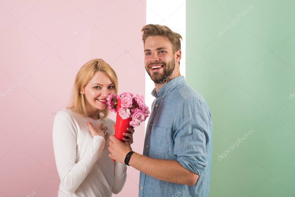 Man congratulates woman birthday anniversary holiday, pastel background. Couple in love celebrating holiday. Man gives bouquet flowers to girlfriend. Gift concept. Couple date bouquet flowers gift