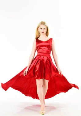 Dress rent service, fashion industry. Woman wears elegant evening red dress, white background. Girl blonde posing in dress. Lady rented fashionable dress for visiting event. Dress rent concept