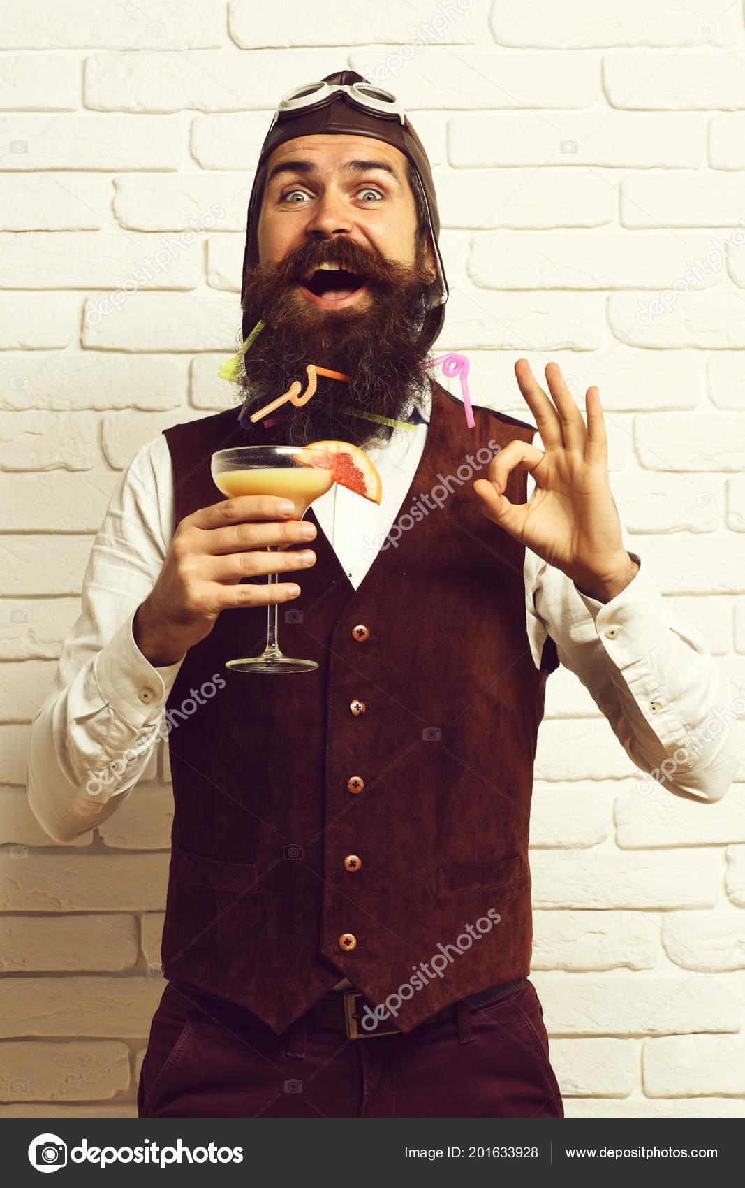 7612d1f13397f Guapo con barba hombre aviador con barba larga y bigote en la cara feliz  con vidrio de Cóctel alcohólico en chaleco de cuero de ante vintage con  sombrero y ...