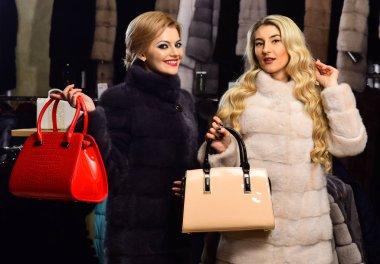Women in fur coats with bags in fur shop.
