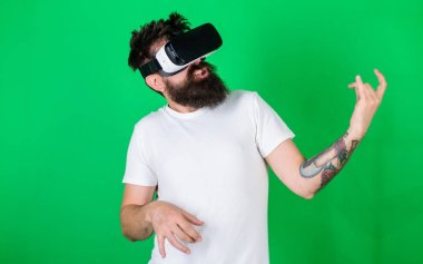 Hipster guitarist on enthusiastic face use modern technology for entertainment. Guy with VR glasses learn to play music on guitar. VR musician concept. Man with beard in VR glasses, green background