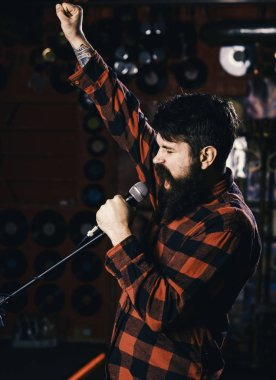 Musician with beard and mustache singing song in karaoke. Hipster likes to sing on stage. Man with enthusiastic face holds microphone, singing song,