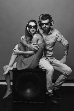 Technologies and music concept. Couple in love sits on black loudspeaker on red background