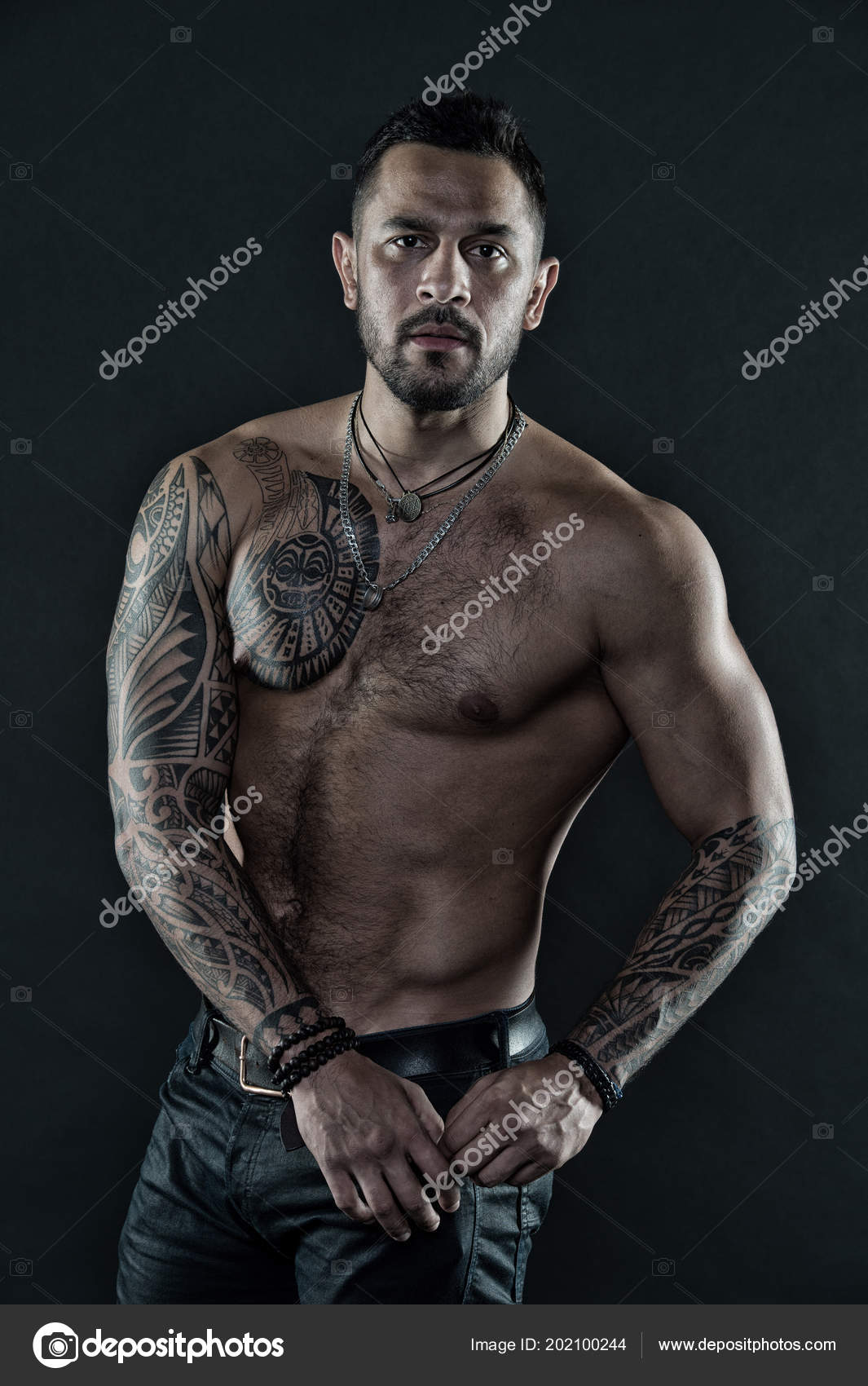 9f4f5ee41 Bearded man with tattooed body. Man with sexy bare torso in jeans. Tattoo  model with six pack and ab. Athlete or sportsman with muscular chest and  belly.