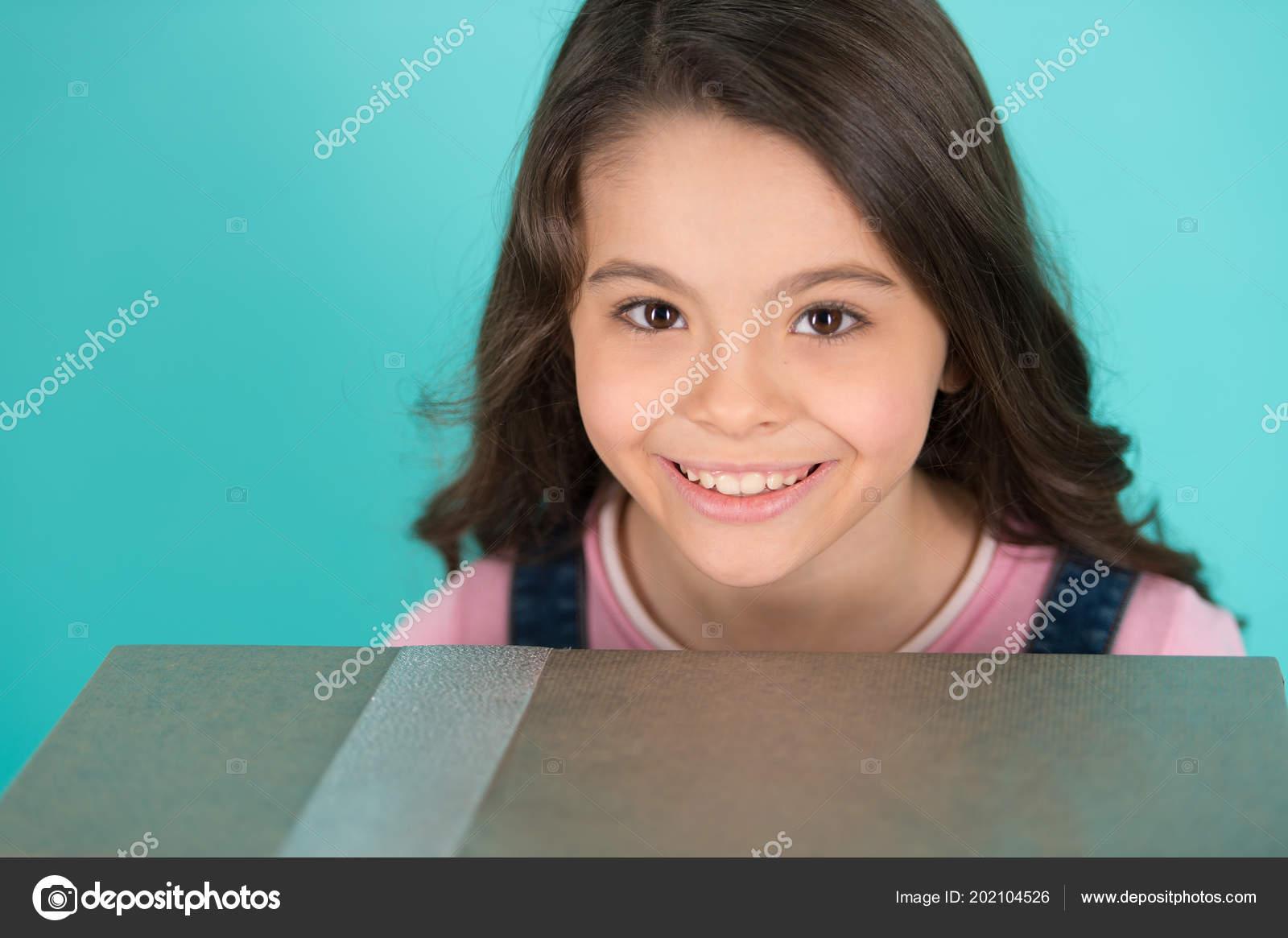 Cara feliz niño tiene fondo turquesa caja de regalo grande. Carita feliz  adorable peinado rizado de niña celebrar cumpleaños.