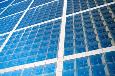 Building facade with blue glass windows. Modern architecture and structure. Construction and design. Commercial property or real estate. Perspective and future concept