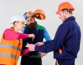 Fotografie Men in hard hats and uniform and young woman.