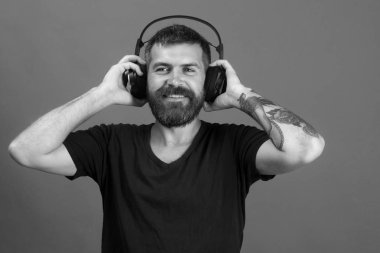 Singer with beard and happy face listens to music. Man holds headphones on blue background. Dj with beard