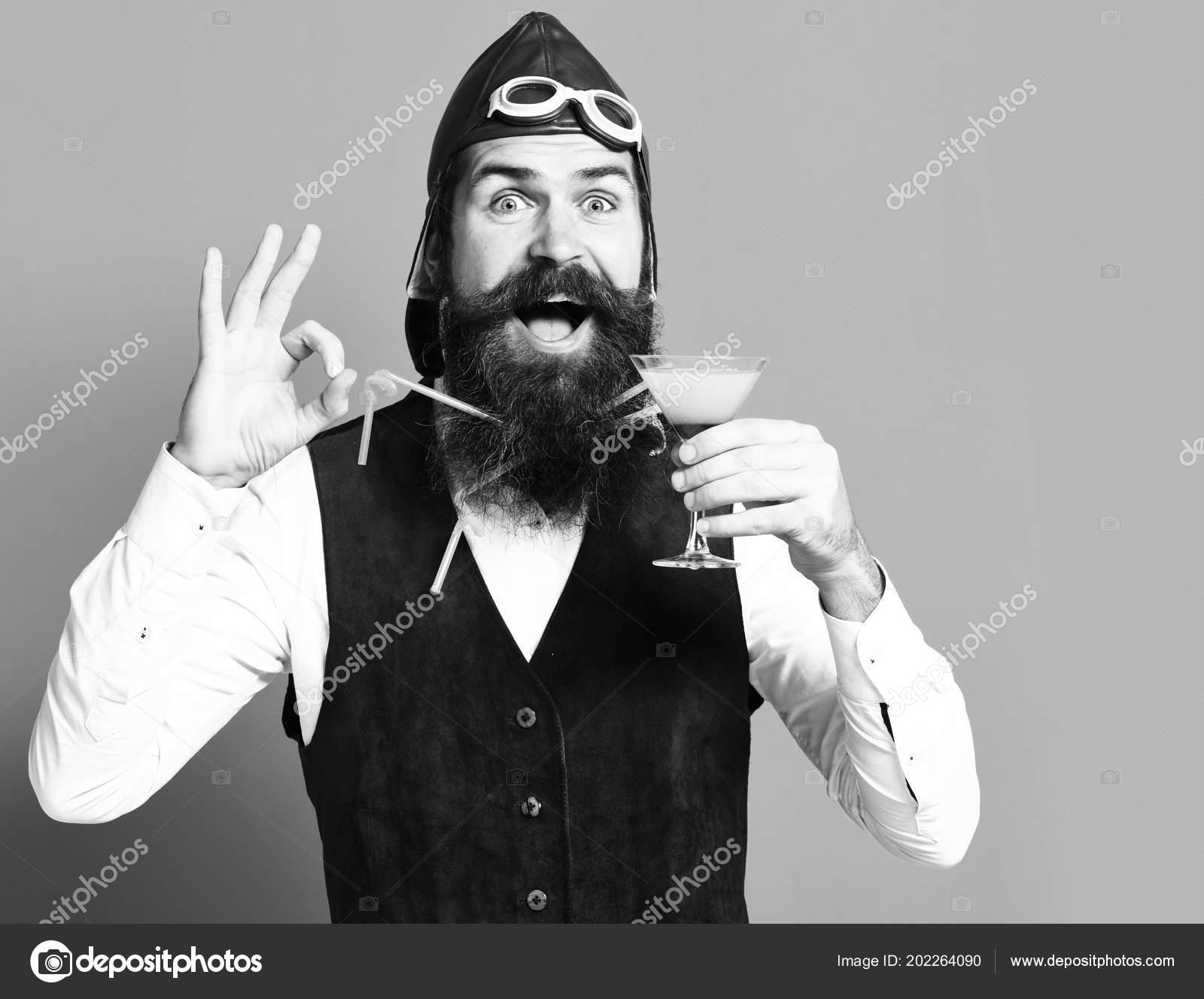 24943ee59c991 Guapo con barba piloto o aviador hombre con barba larga y bigote cara feliz  con vaso de bebida alcohólica en chaleco de cuero de ante vintage con  sombrero y ...