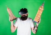 Muž na zmatený obličej studium architektury či designu ve virtuální realitě. Chlap v Vr brýle drží Big Ben a Empire State Building. 3D návrhu koncepce. Muž s plnovousem Vr brýle, zelené pozadí