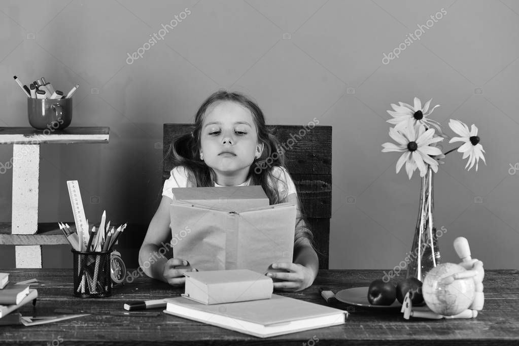 Back to school and childhood concept. Schoolgirl sits at desk with colorful stationery, books and flowers