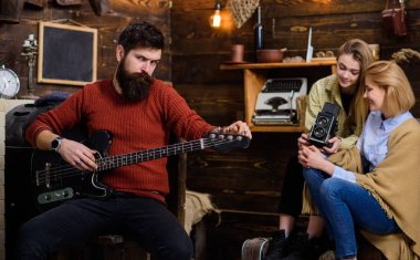 Bearded man in terracotta knitted pullover and black jeans wearing ring with huge gem stone, fashion concept. Man with stylish beard posing with electrical guitar, musical instruments store promo