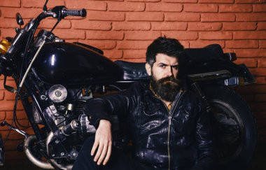Bikers lifestyle concept. Man with beard, biker in leather jacket near motor bike in garage, brick wall background. Hipster, brutal biker on pensive face in leather jacket sits, leans on motorcycle
