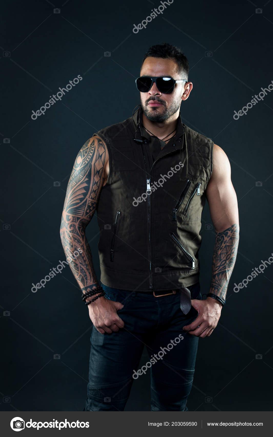 b93bf6eab470ae Tattoo model met baard op ongeschoren gezicht. Bebaarde man met tatoeage op  sterke armen. Mode macho in trendy zonnebril. Fashion stijl en trend — Foto  van ...